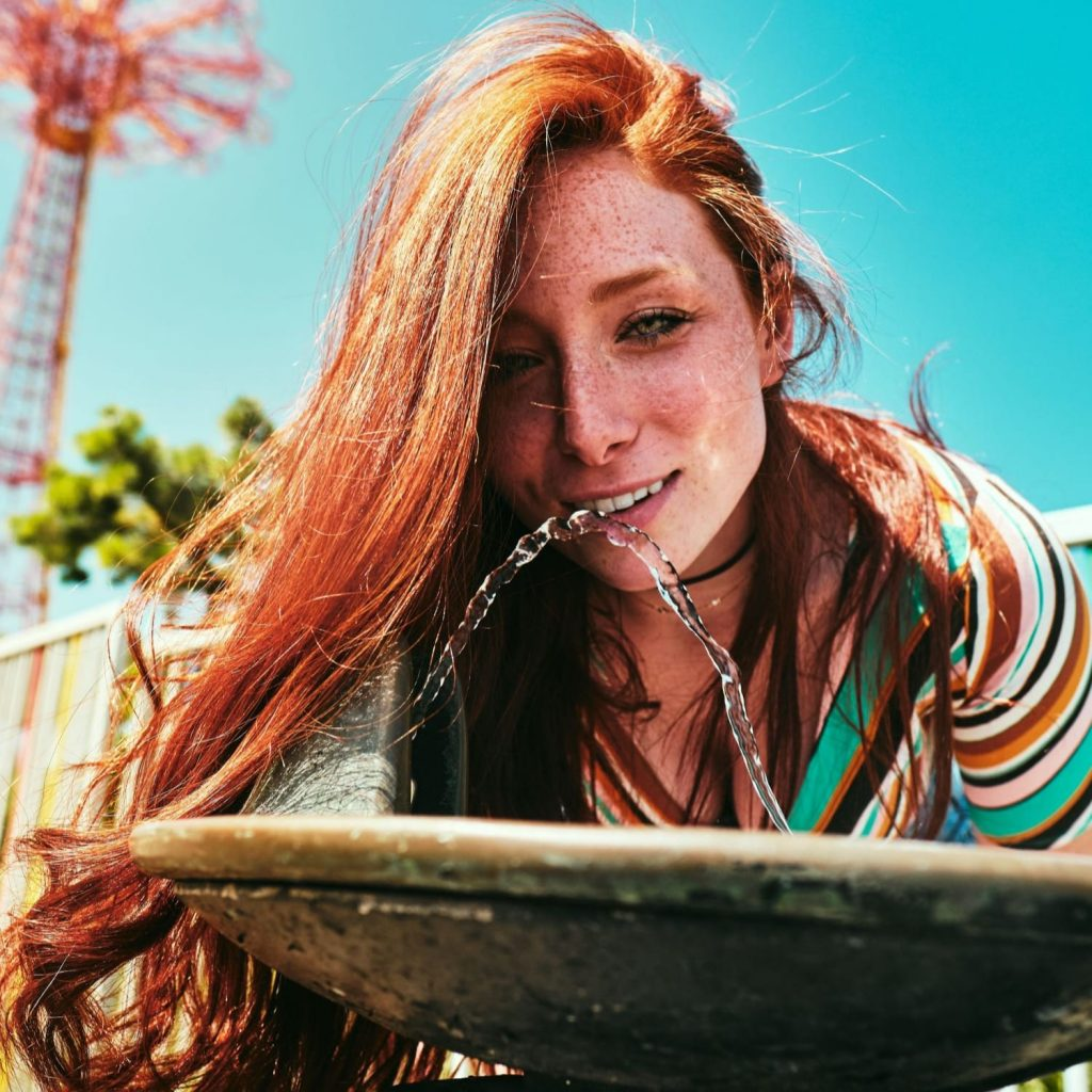 Lovely red haired girl drinking from a water fountain